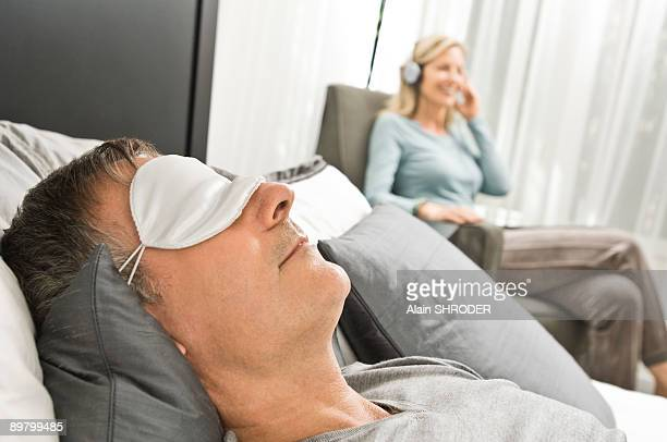 Man wearing an eye mask and his wife listening to music in the background