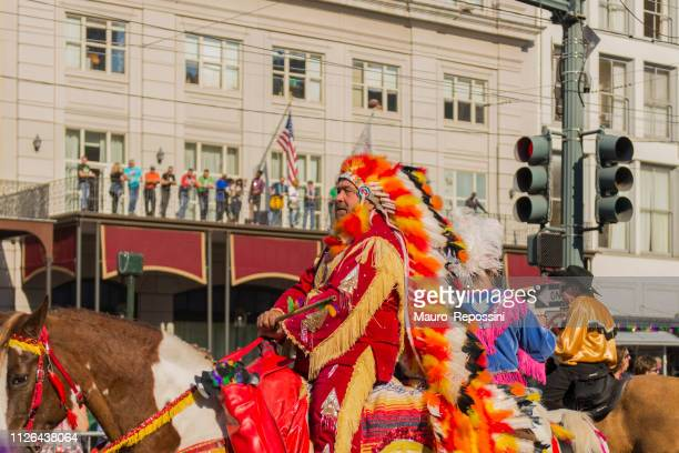 a man wearing an indian costume on a horse in the street during the mardi gras celebration at new orleans carnival, louisiana, usa . - mardi gras fun in new orleans stock photos and pictures