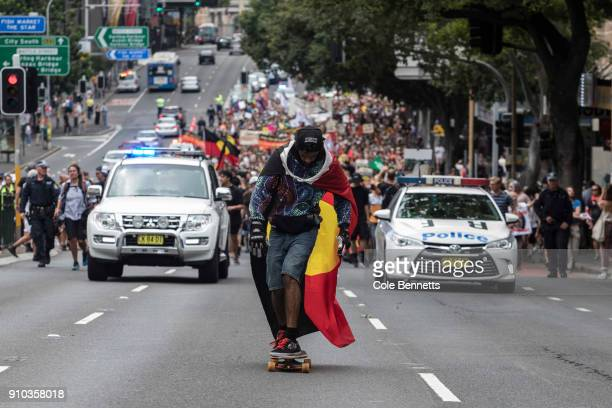 A man wearing an Indigenous flag as a cape on a skateboard rides ahead of the thousands strong Invasion day March on January 26 2018 in Sydney...
