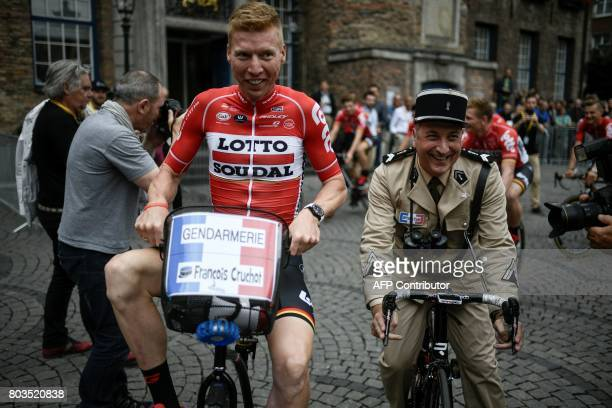 A man wearing an old French gendarme uniform performing rides with Germany's Marcel Sieberg during the parade of the team presentation ceremony in...