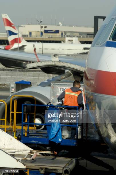 Man wearing an orange highviz tabard loading an LD3 baggage container on to an American Airlines Airbus A300600R parked at the terminal with a...