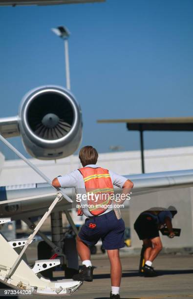 man wearing an orange highviz tabard standing on the airstairs and another under wing of an Embraer ERJ145 parked with an AE3007 engine intake behind