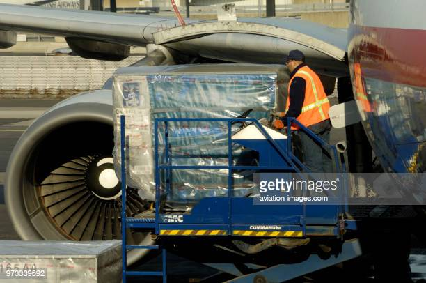 Man wearing an orange highviz tabard unloading LD3 containers from an American Airlines Airbus A330600R