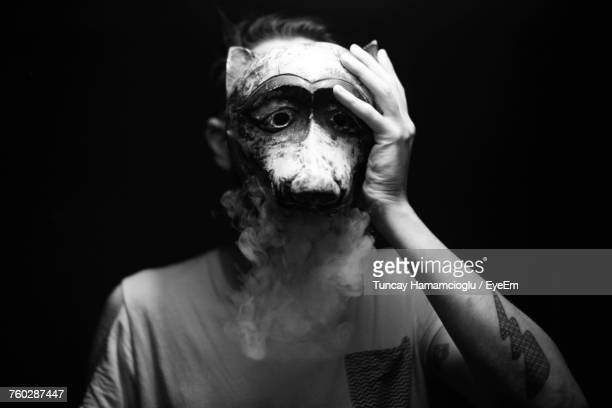 Man Wearing Animal Mask While Standing Against Black Background