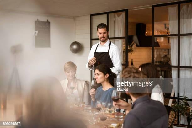 Man wearing apron looking at people tasting wine at workshop