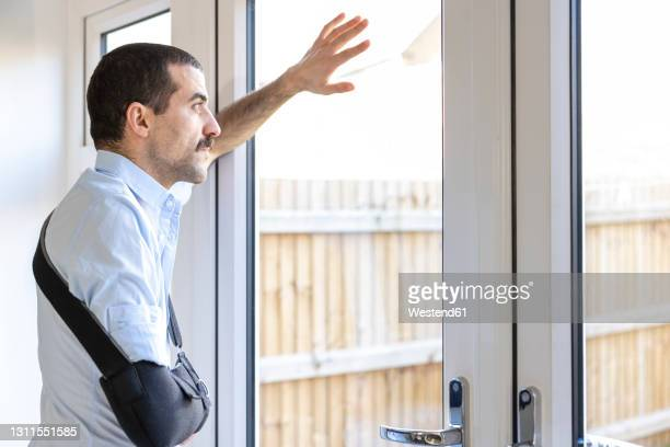 man wearing arm sling looking through window while standing at home - side view stock pictures, royalty-free photos & images