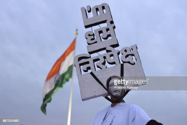 A man wearing artwork written 'I am Dharam' Nirpeksh in front of a giant Indian flag during protest to mark black day on the 25th anniversary of...