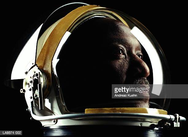 man wearing astronaut helmet, close-up - astronaut stock-fotos und bilder