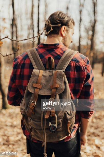 Man wearing backpack on his back in the forest