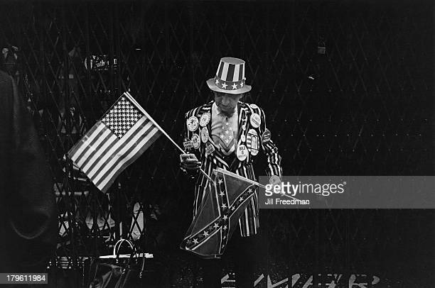 A man wearing badges carries American flags on a New York City street 1975