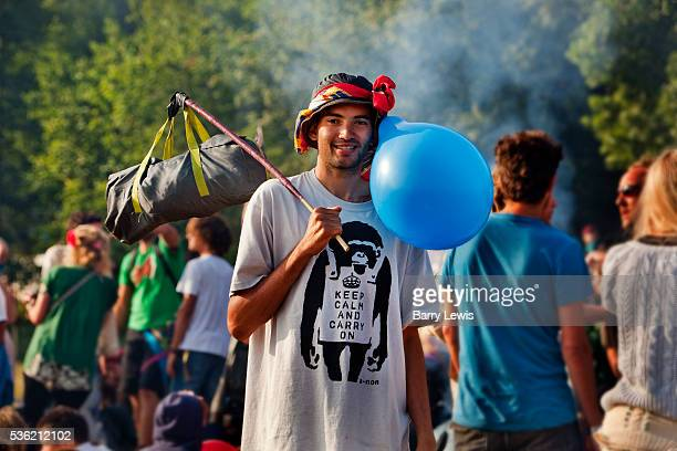 Man wearing balloon Banksy Tshirt withe the slogan 'Keep Calm and Carry On' the morning after in the stone circle Glastonbury Festival 2010