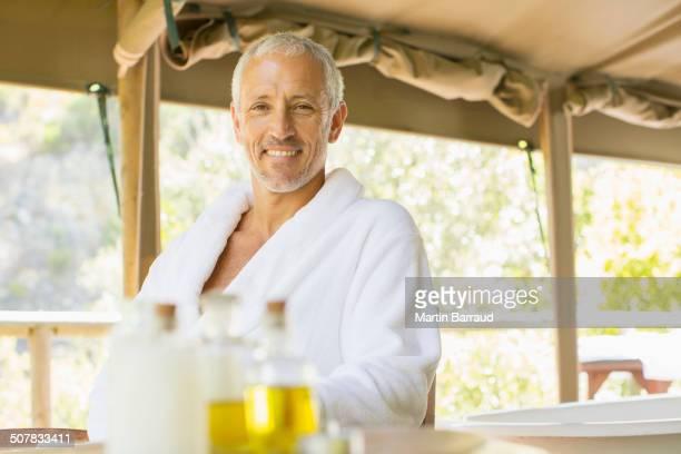 Man wearing bathrobe at table