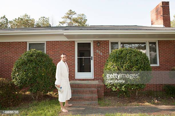 man wearing bathrobe outside his home - bathrobe stock pictures, royalty-free photos & images