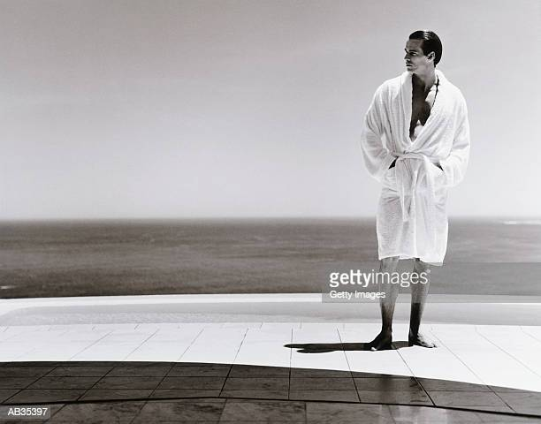 Man wearing bathrobe standing by swimming pool (B&W)