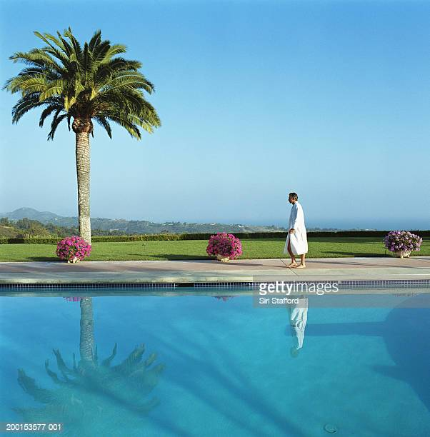 man wearing bathrobe, walking along side pool - poolside stock pictures, royalty-free photos & images