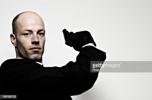 Mann mit schwarzen Handschuhen und posieren mit Waffe