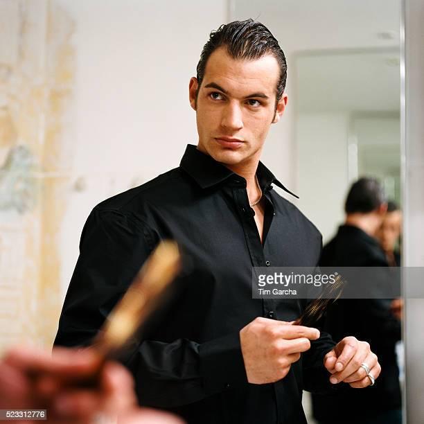 Man Wearing Black Shirt Looking in Mirror