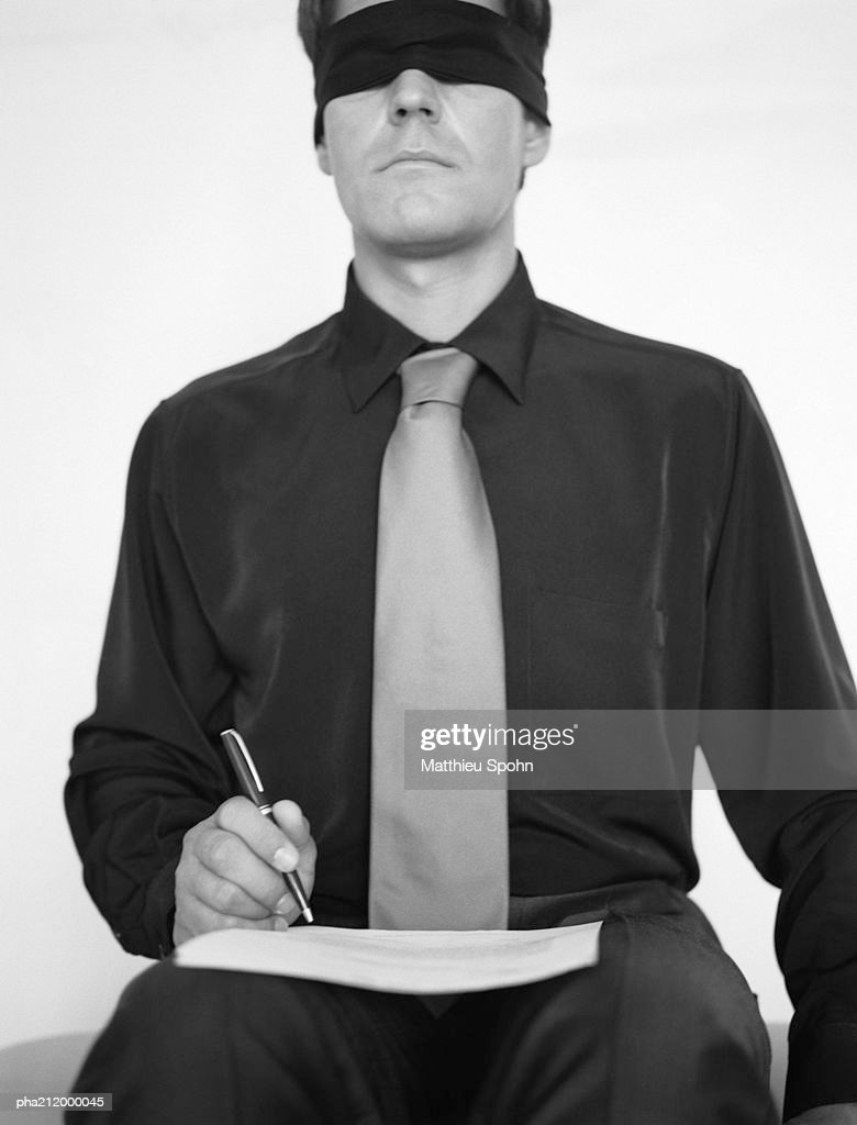 Man wearing blindfold, writing in a book, b&w. : Stockfoto