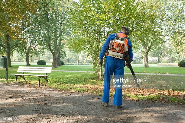 man wearing blue coveralls removing leaves from footpath in park - street sweeper stock pictures, royalty-free photos & images
