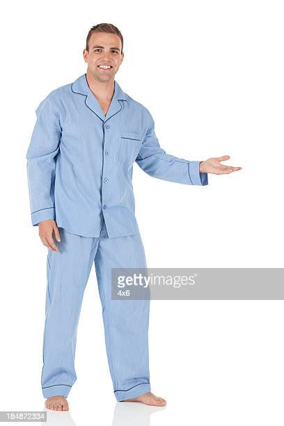 man wearing blue pajamas and presenting - pajamas stock pictures, royalty-free photos & images