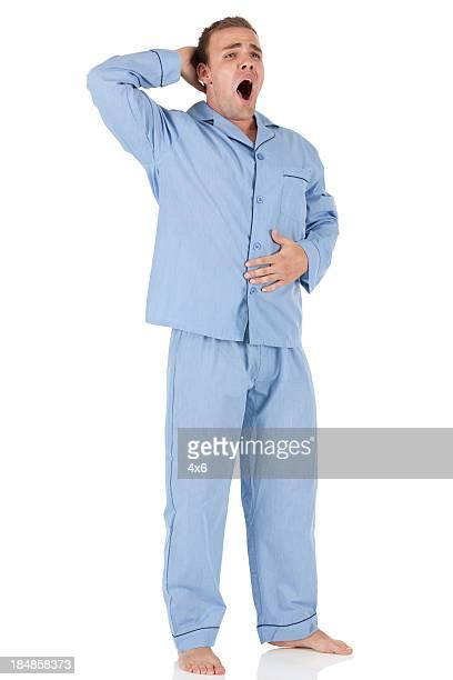 Man wearing blue pajamas and yawning