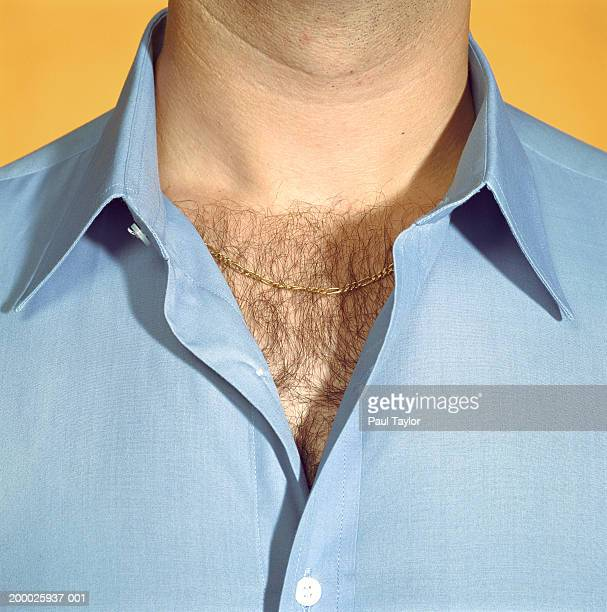 Man wearing blue shirt with chest hair visible, close-up