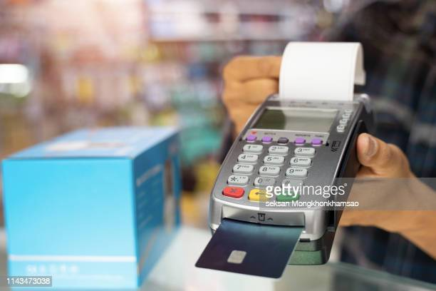 man wearing blue white square pattern shirt holding up credit card payment terminal in front of camera, closeup angle - inserting stock pictures, royalty-free photos & images