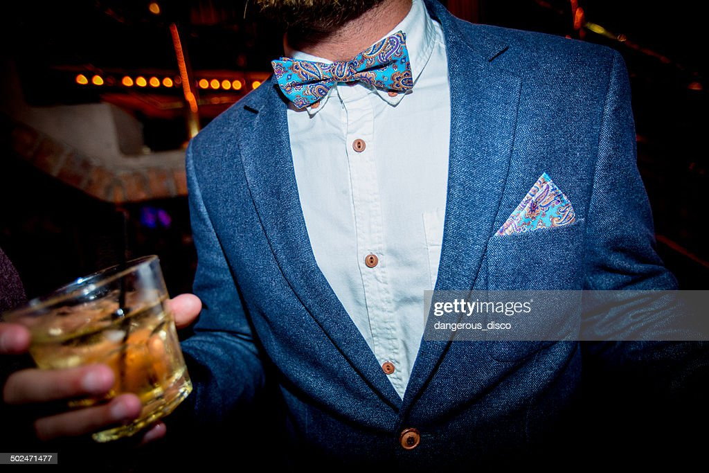Man wearing bow tie and jacket holding a drink : Foto de stock