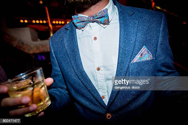 man wearing bow tie and jacket holding a drink - revers stock-fotos und bilder