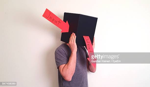 Man Wearing Box With Input And Output Arrow Sign Against White Background