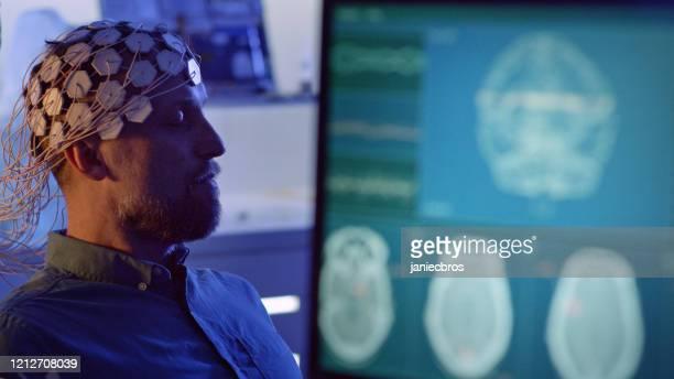man wearing brainwave scanning headset. - eeg stock pictures, royalty-free photos & images