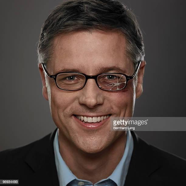 Man wearing broken glasses, smiling