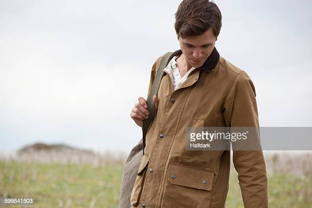 man wearing brown jacket carrying backpack, close-up - brown coat stock pictures, royalty-free photos & images
