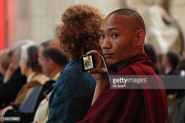 A man wearing Buddhist robes uses his smartphone to film His Holiness the Dalai Lama addressing the audience in St Paul's Cathedral after receiving...