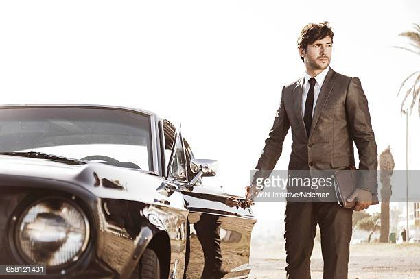 Man wearing business suit gets out from car