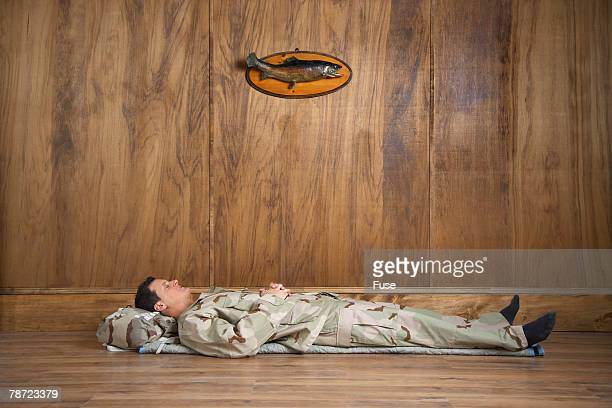 Man Wearing Camouflage Sleeping on Floor in Wood-paneled Room