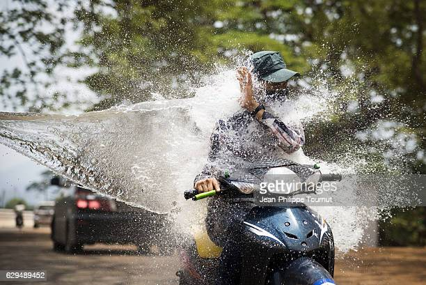 Man wearing cap splashed in the face by a bucket of water while riding a motorbike on the road during Thingyan Water Festival, Myanmar's traditional New Year Festival, in April 2016