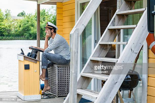 man wearing captain's hat having a trip on a house boat - sailor hat stock pictures, royalty-free photos & images