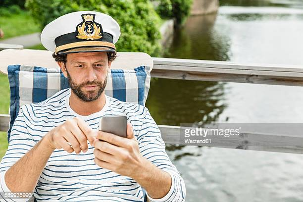 Man wearing captain's hat looking at cell phone