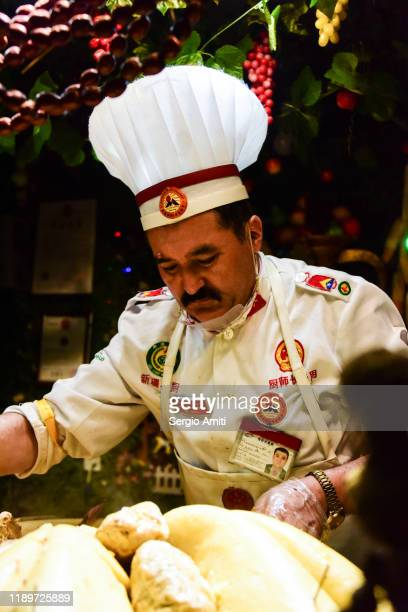 man wearing chef's hat arranging meats in night market in urumqi - sergio amiti stock pictures, royalty-free photos & images