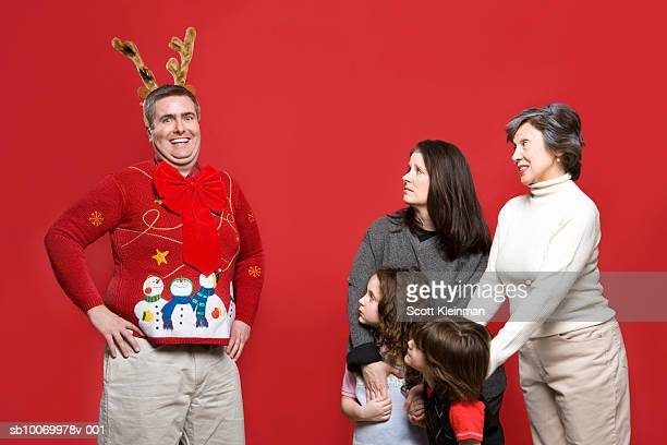 Man wearing Christmas sweater and reindeer antlers with embarrassed family, studio shot