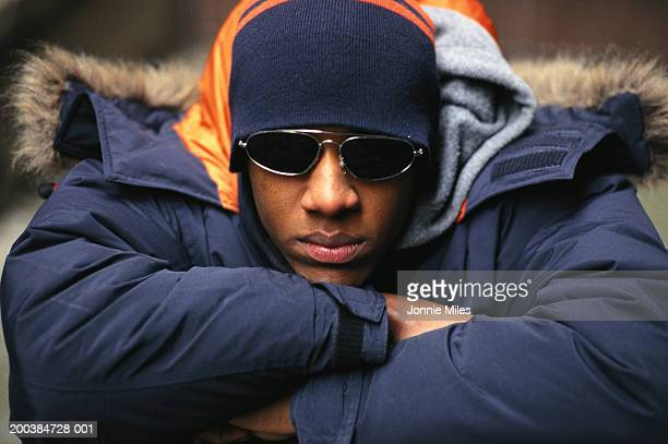 Man wearing coat, hat and sunglasses, resting chin on arms, close-up