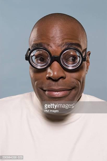 Man wearing coke bottle glasses, smiling, close-up