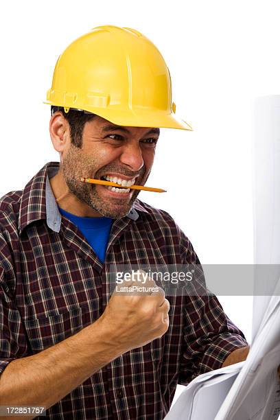 Man wearing construction hat blueprints gesturing and making face
