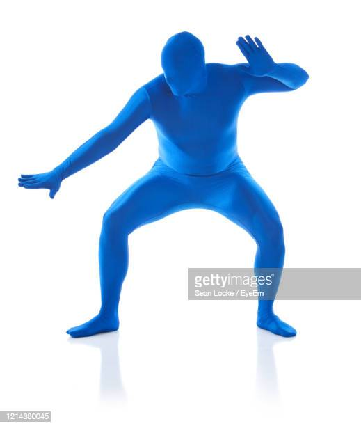 man wearing costume gesturing over white background - bodysuit stock pictures, royalty-free photos & images
