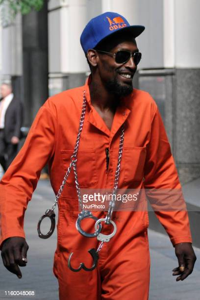 A man wearing cuffs and orange overalls walks past the courthouse in Philadelphia PA on August 6 2019