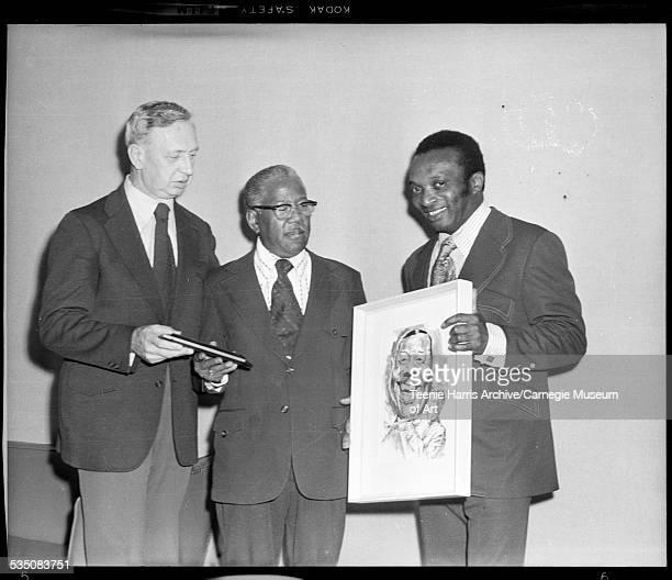 Man wearing dark jacket and Roy Eldridge presenting plaque to Walt Harper holding caricature Pittsburgh Pennsylvania 1969