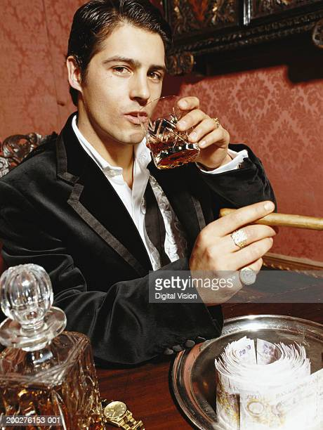 man wearing dinner jacket, drinking whisky and smoking cigar, portrait - smoking jacket stock photos and pictures