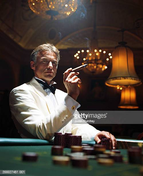 man wearing dinner jacket smoking cigar in casino, portrait - smoking jacket stock photos and pictures