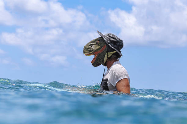 Man wearing dinosaur mask in sea during sunny day